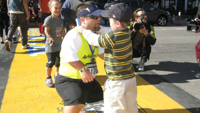 PHOTO: John Young, 47, bends has his son, Owen, 10, puts a medal over his head at the Boston Marathon finish line on April 30, 2013.