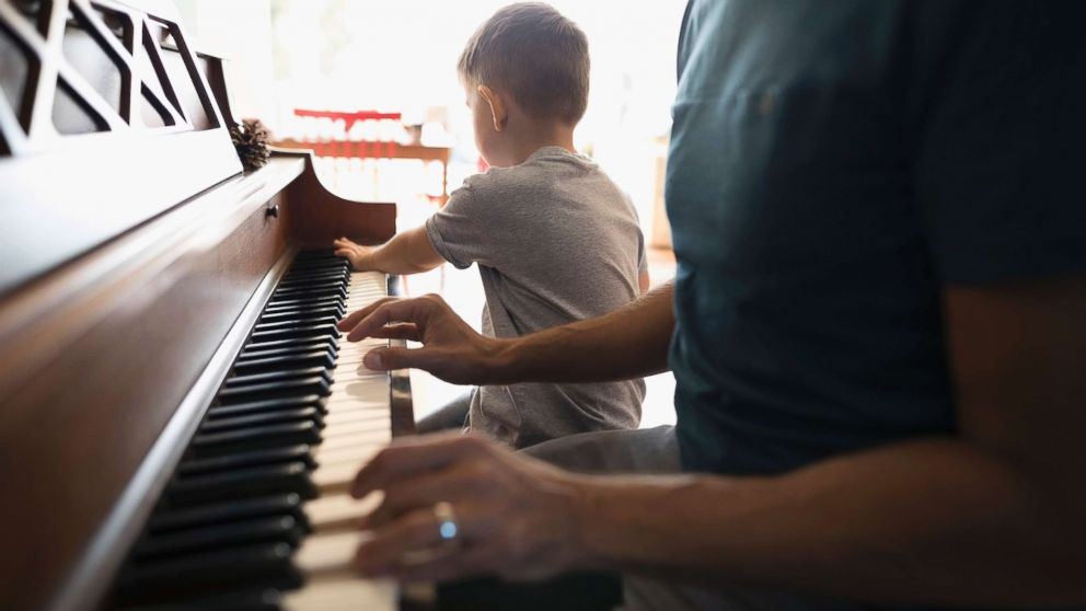 A child is seen pictured playing a piano seen this undated stock photo.