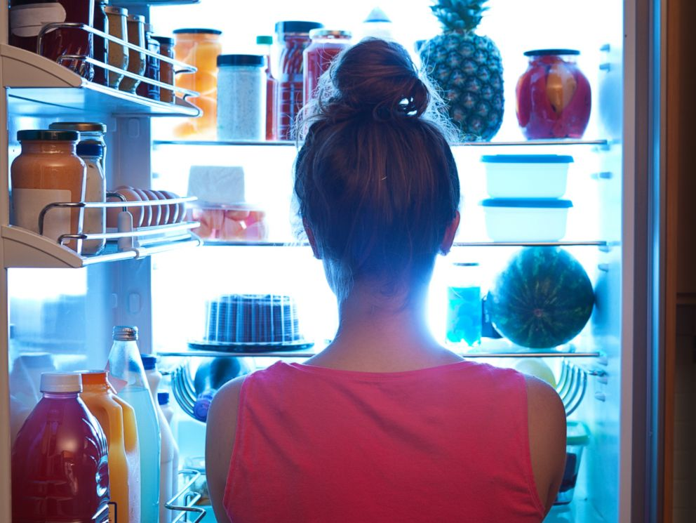 PHOTO: A woman is pictured standing in front of the open refrigerator late at night in this undated stock photo.