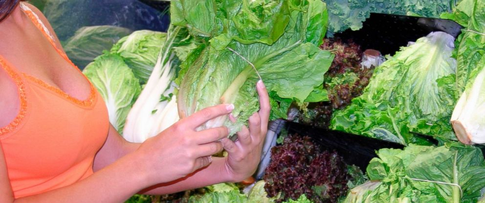PHOTO: A woman is pictured holding romaine lettuce at a store.