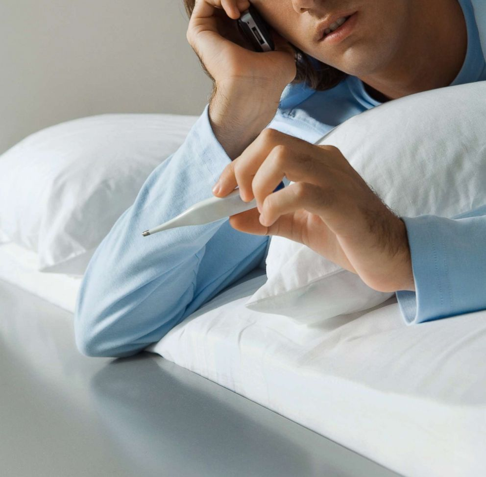 PHOTO: A man is pictured lying in bed, using a cell phone and holding up thermometer in this undated stock photo.