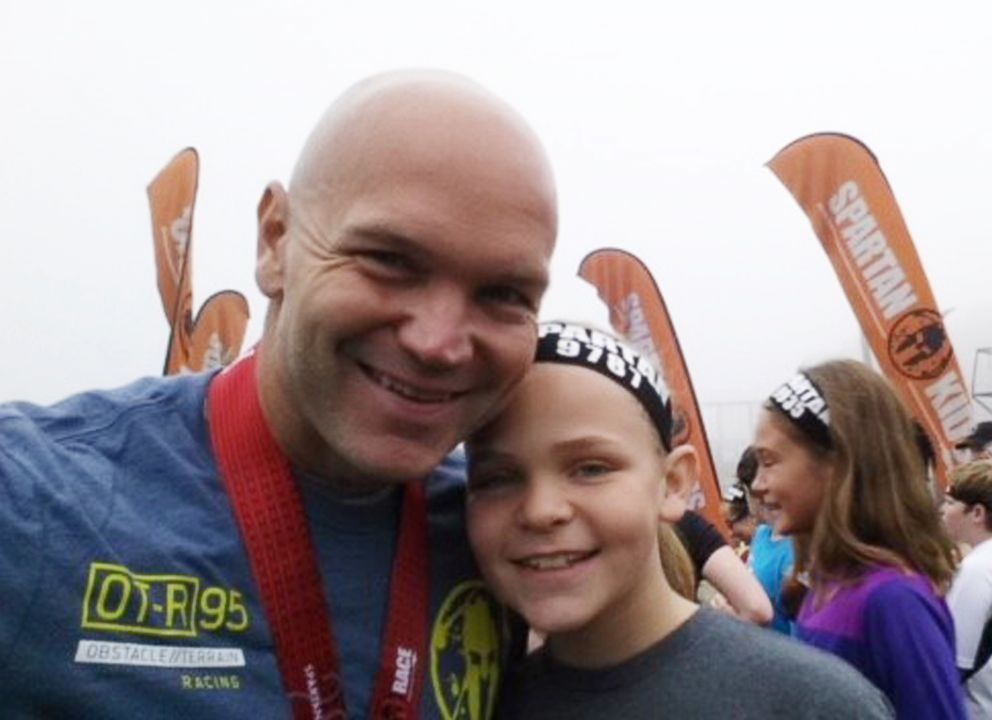 PHOTO: Andy Bell, 45, poses with one of his daughters after completing a Spartan race.