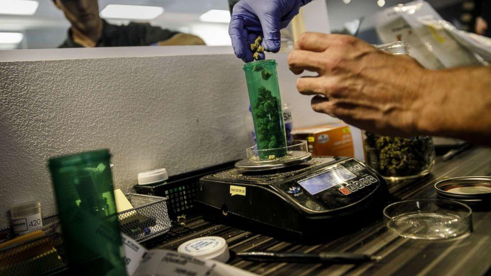 An employee dispenses a customer's order at a Medical Marijuana facility, in Santa Ana, Calif., Jan. 1, 2018.