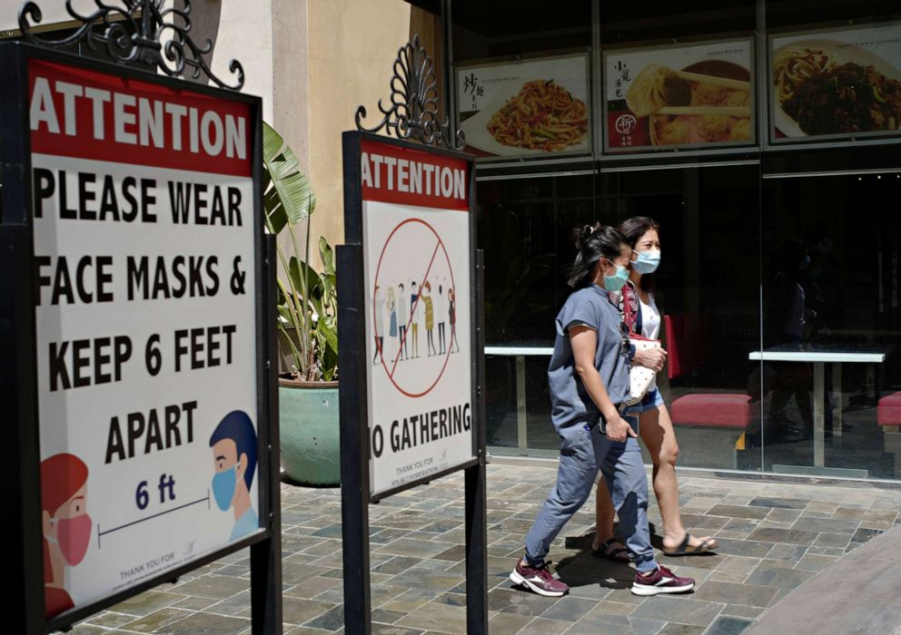 PHOTO: Customers wear face masks in an outdoor mall with closed business amid the COVID-19 pandemic in Los Angeles, June 11, 2021.