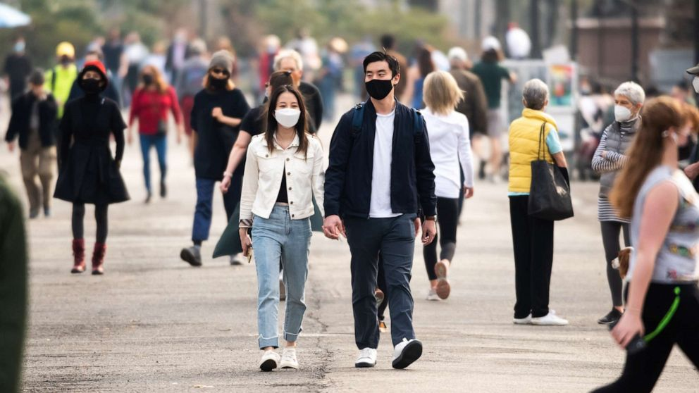 PHOTO: People wear face masks while walking in Central Park on March 11, 2021, in New York City.