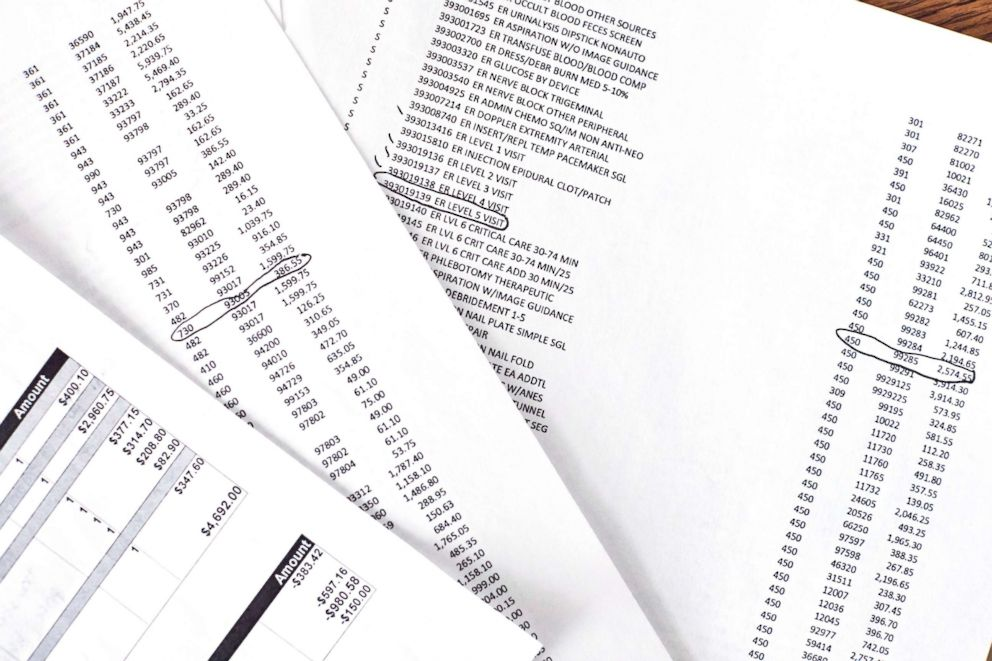 PHOTO: Matt Gleason compares charges on his medical bill with the chargemaster he received from Atrium Health.