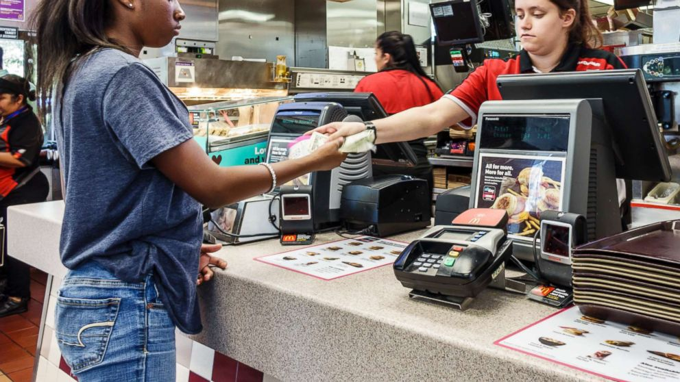 A McDonalds cashier gives change to a young customer in Vero Beach, Fla., Oct. 23, 2016.