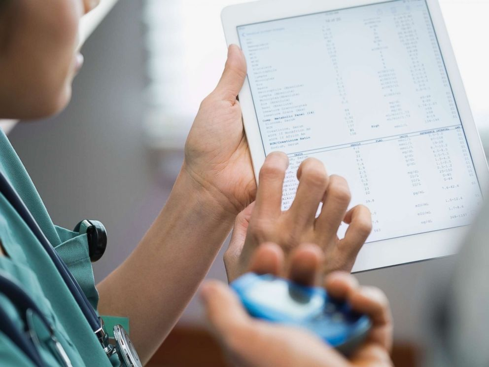 PHOTO: A doctor looks at health records with a patient in an undated stock photo.