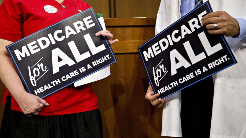 Attendees hold signs while waiting for a health care bill news conference to begin on Capitol Hill in Washington, Sept. 13, 2017.