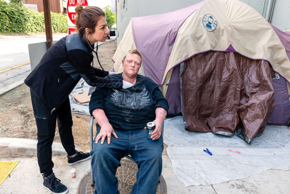 PHOTO: Saban Community Clinic physician assistant Negeen Farmand checks Jennifer Millar at a homeless encampment near a Hollywood freeway one morning.