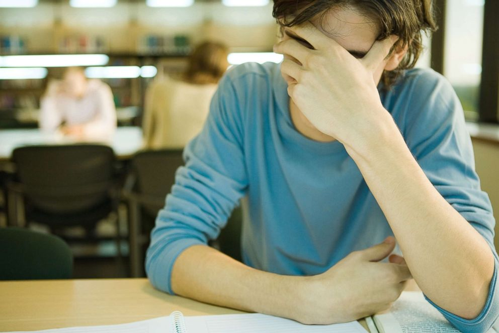 A college student is pictured covering his face in this undated stock photo.