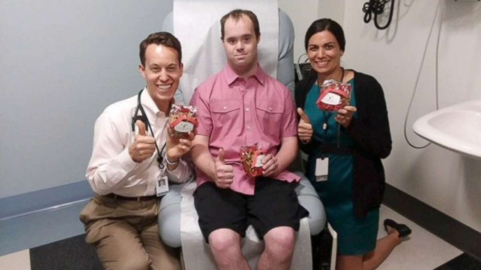 Michael Clayburgh, center, poses with Dr. Brian Skotko, left, and Amy Torres at Massachusetts General Hospital in Boston.