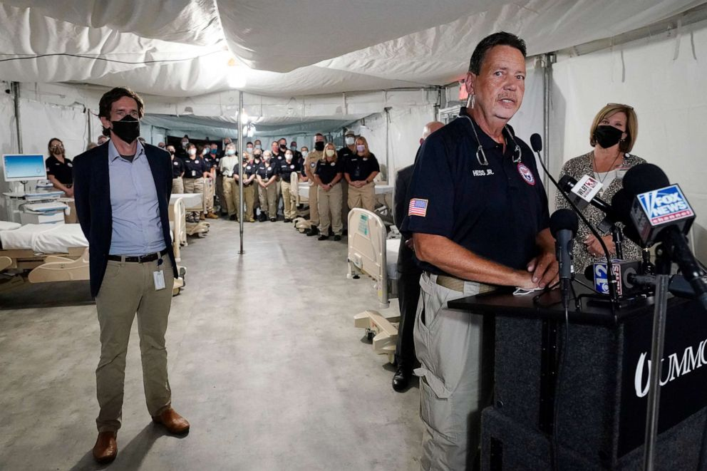 PHOTO: Cmdr. Richard Hess Jr., center, with the National Disaster Medical System, speaks to how he and his team will help staff the field hospital in a garage at the University of Mississippi Medical Center in Jackson, Miss., Thursday, Aug. 12, 2021.