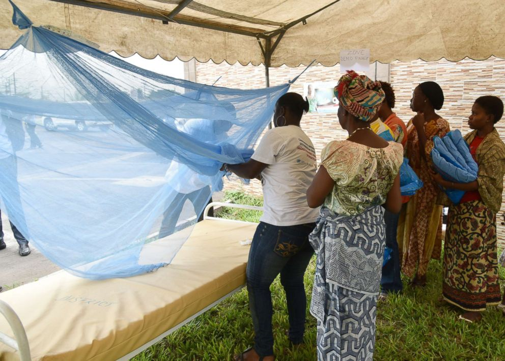 PHOTO: People show how to put a mosquito net on a bed during a free insecticide-treated mosquito nets distribution, April 24, 2015, in Abidjan, Ivory Coast.
