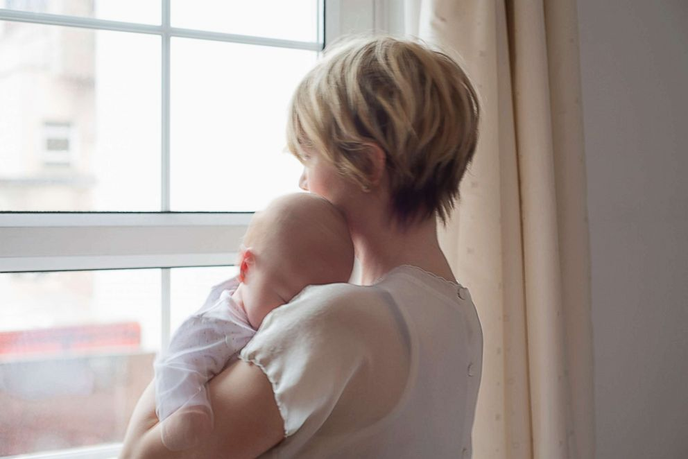 PHOTO: A mother holds her sleeping baby while looking out the window in this undated stock photo.