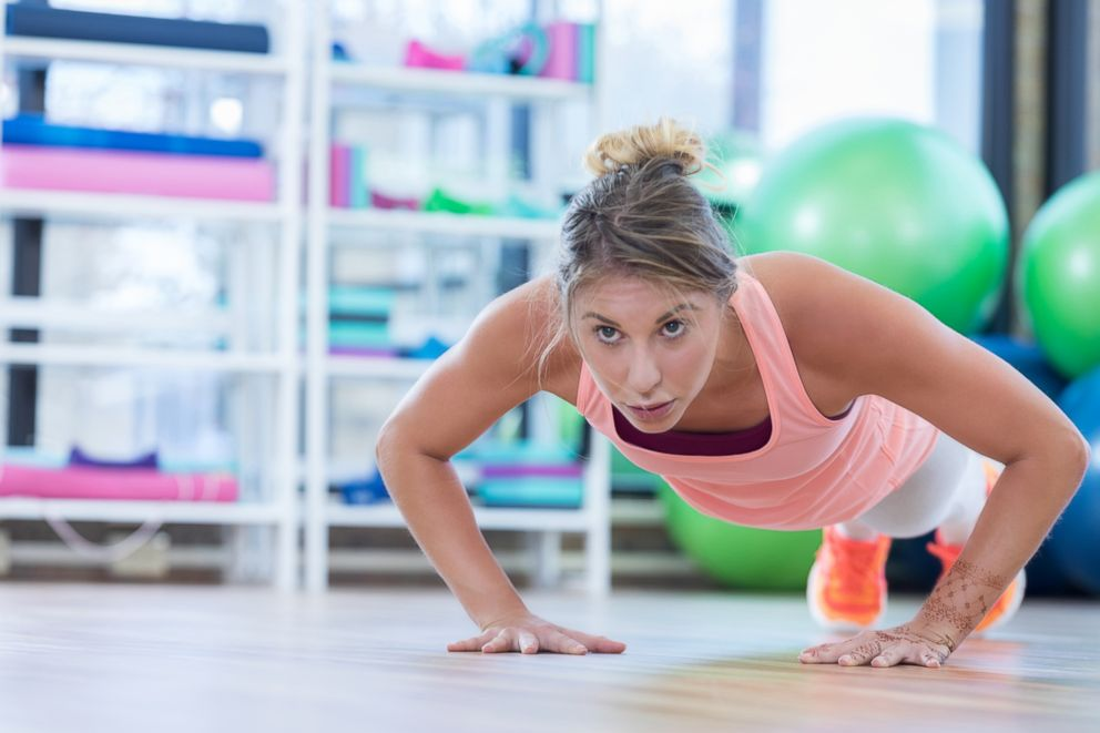 A woman does push ups while working out in a gym in this stock image.