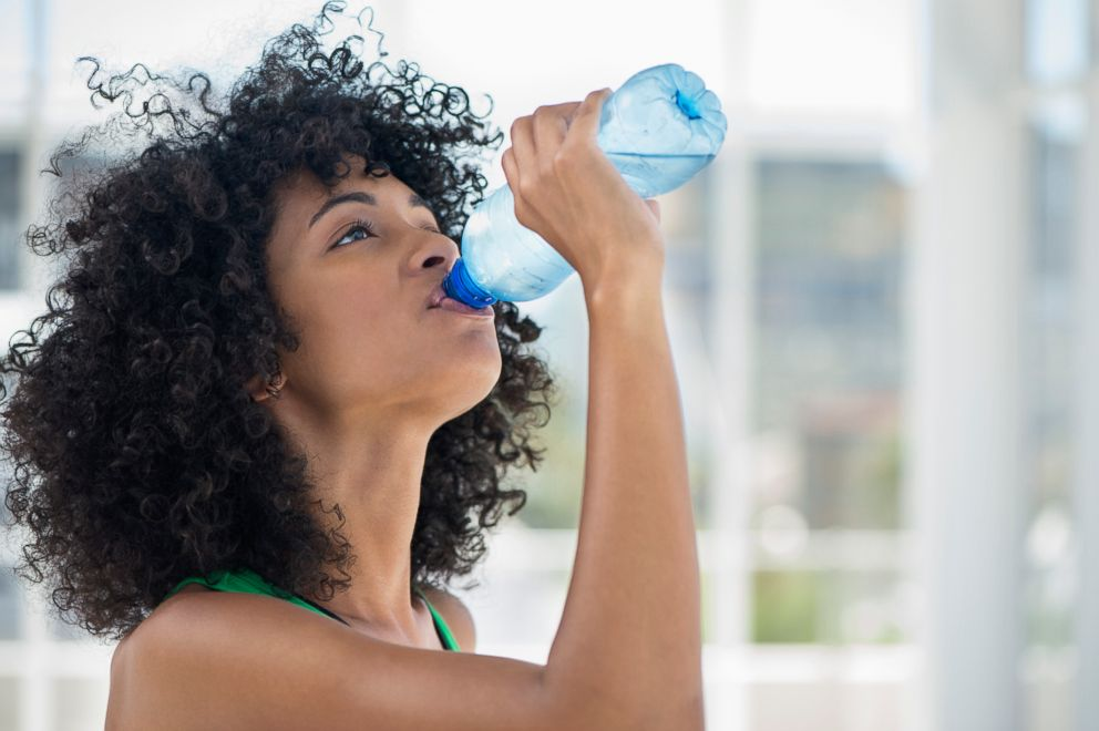 A woman is drinking more water for a new year's resolution seen in this stock image.