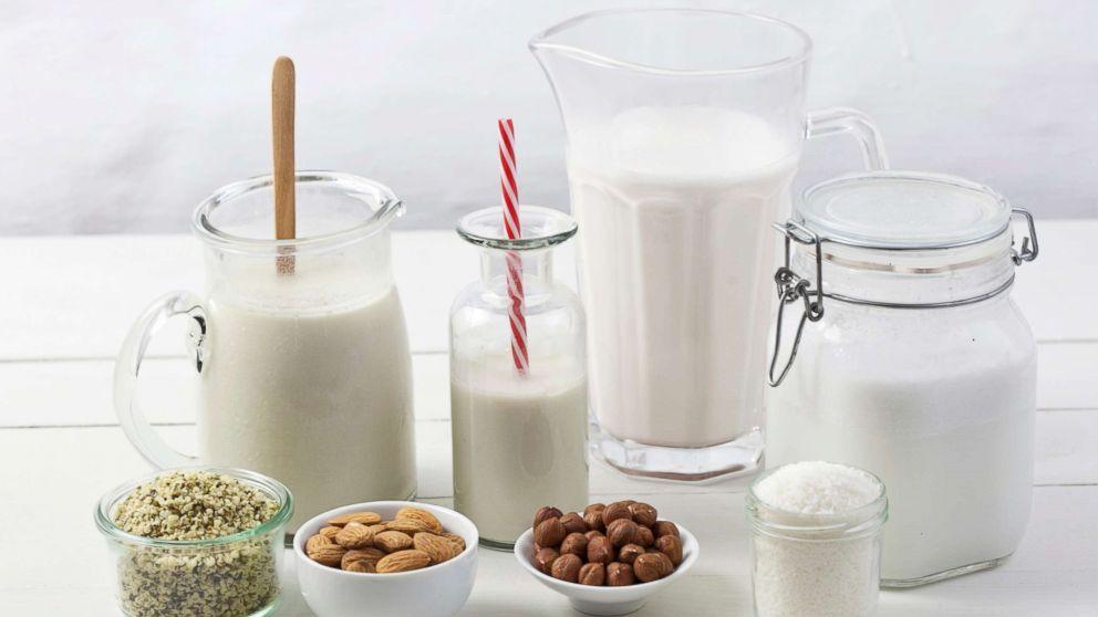 Various types of vegan milk with ingredients.