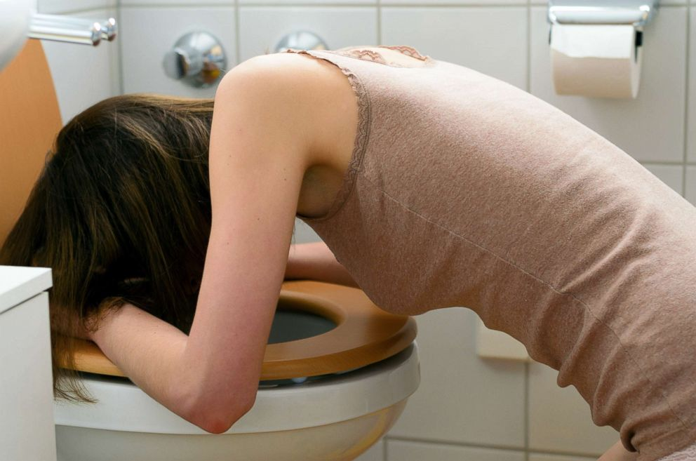 PHOTO: A woman leans over the toilet.