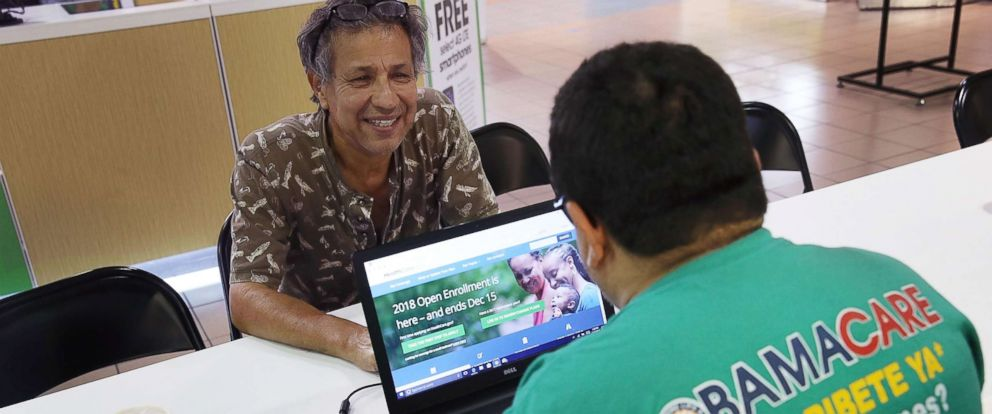 PHOTO: Rudy Figueroa, right, speaks with Marvin Mojica as he shops for insurance under the Affordable Care Act at a store setup in the Mall of America, Nov. 1, 2017 in Miami, Fla.