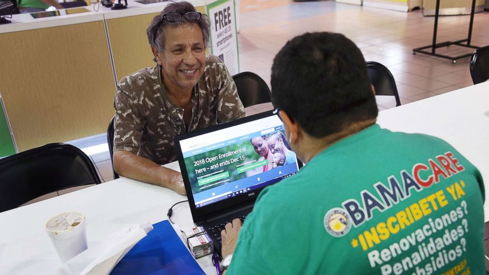 Rudy Figueroa, right, speaks with Marvin Mojica as he shops for insurance under the Affordable Care Act at a store setup in the Mall of America, Nov. 1, 2017 in Miami, Fla.