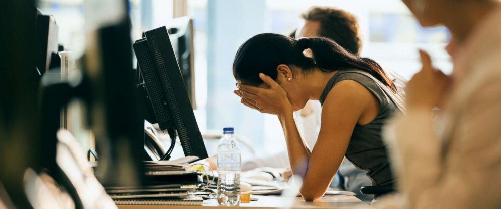 PHOTO: This stock photo depicts a woman at her desk holding her head.