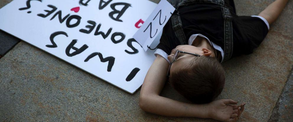 """PHOTO: Pj Lowry, 12, lays on the ground at an overdose prevention """"die in"""" outside Portland City Hall, Sept. 7, 2018. Lowry participated with his mom Merideth Norris, an osteopath and addiction specialist."""