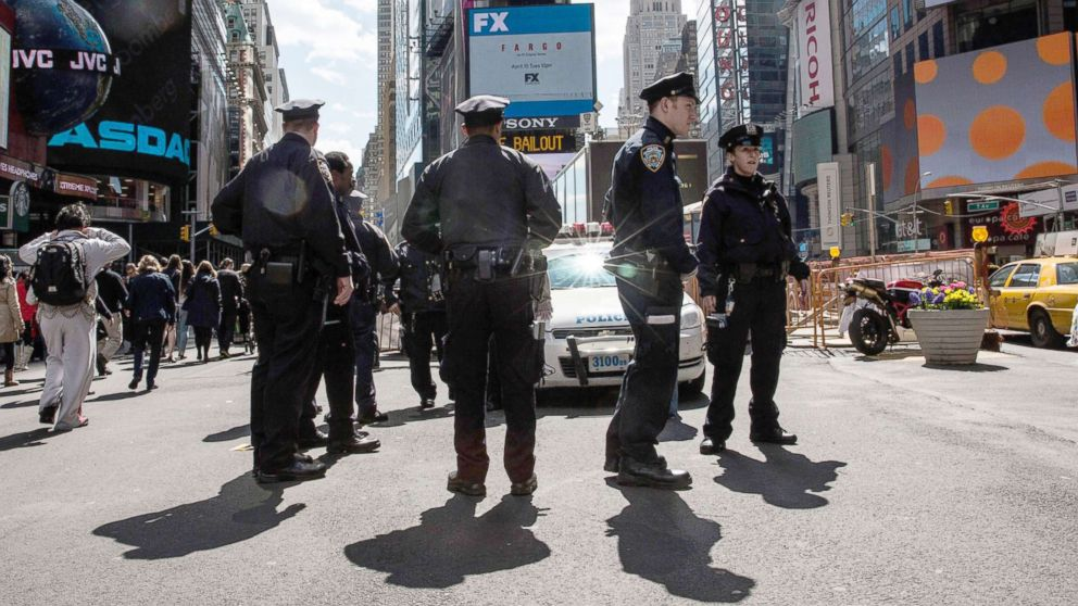 Police officers hold a meeting on the sidewalk while patrolling Times Square, April 9, 2014, in New York City.