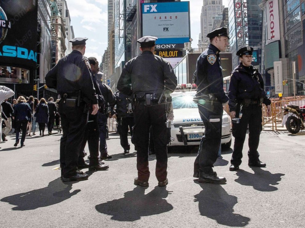 PHOTO: Police officers hold a meeting on the sidewalk while patrolling Times Square, April 9, 2014, in New York City.
