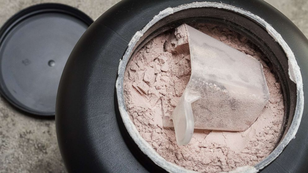 A scoop of fine whey protein powder sits in a container in an undated stock photo.