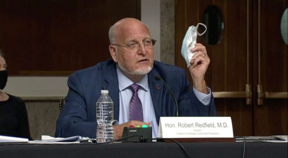 PHOTO: Centers for Disease Control and Prevention Director Dr. Robert Redfield holds up his mask as he speaks at a Senate Appropriations subcommittee hearing, Sept. 16, 2020, in Washington.