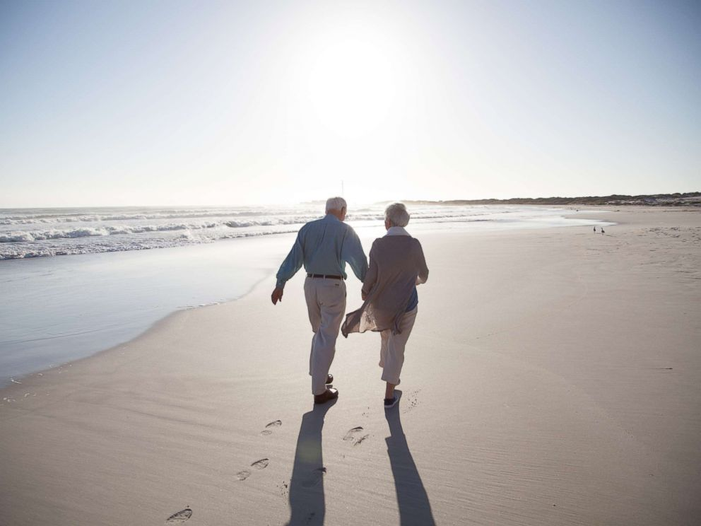 PHOTO: A senior couple enjoying time together walking on a beach at sunset in this undated stock photo.