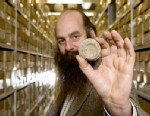PHOTO: Dr Robert Symmons, Curator of the Fishbourne Roman Palace reserve collection, with one of the ceramic discs or gaming pieces, which may actually have been used as toilet paper in Chichester, West Sussex, Jan 17, 2013.