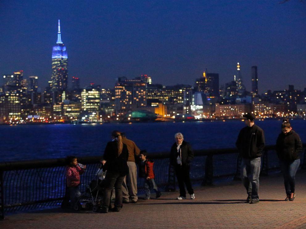 PHOTO: In this April 2, 2014 file photo, people watch the skyline of Manhattan from Hoboken, New Jersey, while the Empire State Building is seen lit up in blue to mark World Autism Day in New York.