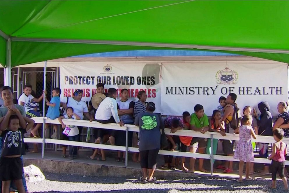 2019 image from video children with parents wait in line to get vaccinated outside a health clinic in Apia Samoa