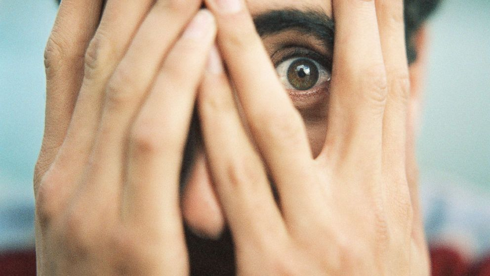 A man covers his face in an undated stock photo.