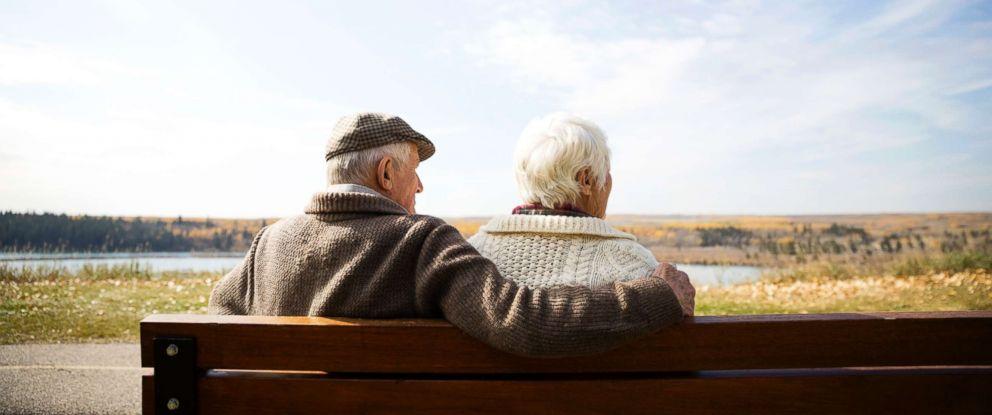 PHOTO: A senior couple sit on bench in this stock photo.