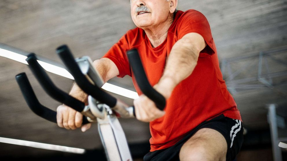 PHOTO: In this undated photograph, a senior man is riding on a spinning bike in a gym.