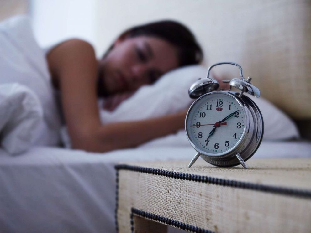 PHOTO: A young woman sleeps with an alarm clock next to her bed in this undated stock photo.