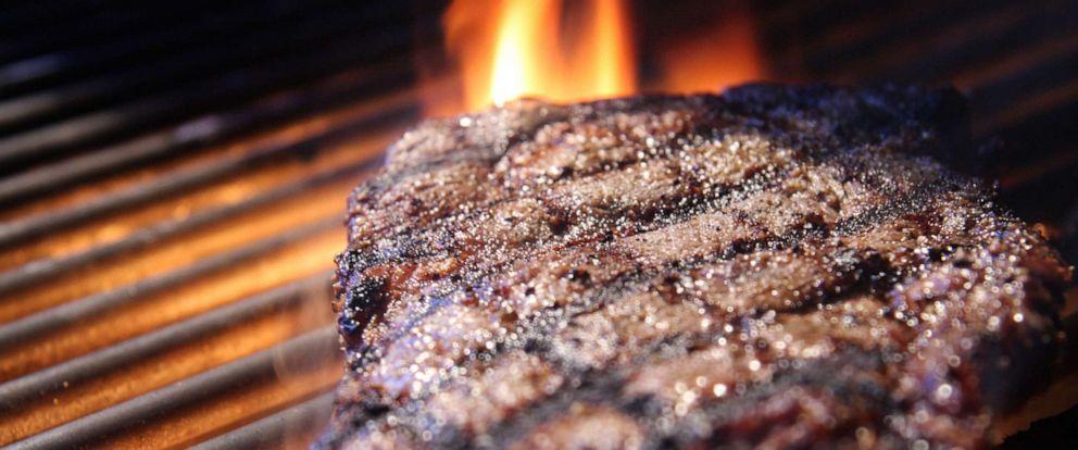 PHOTO: Grilled ribeye steak sitting on a flame.