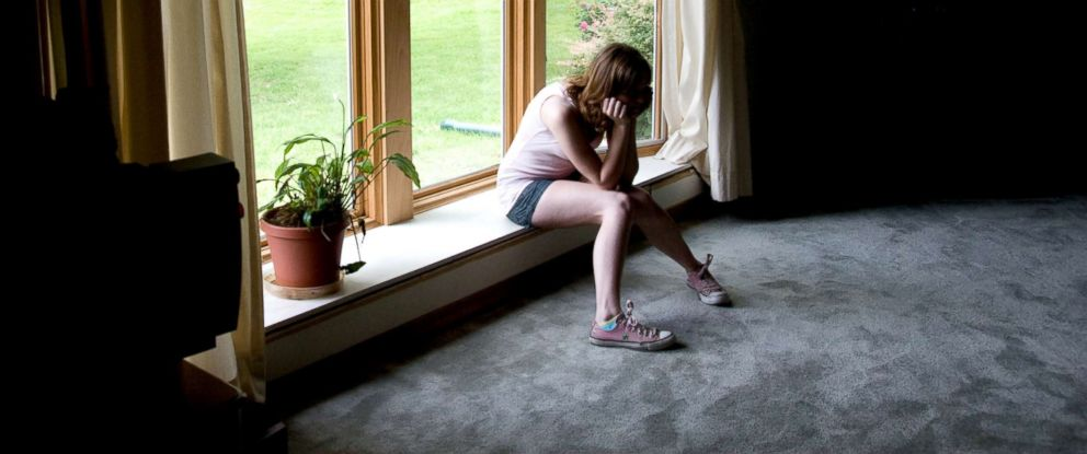 PHOTO: Stock photo of a teen girl sitting in front of a window.