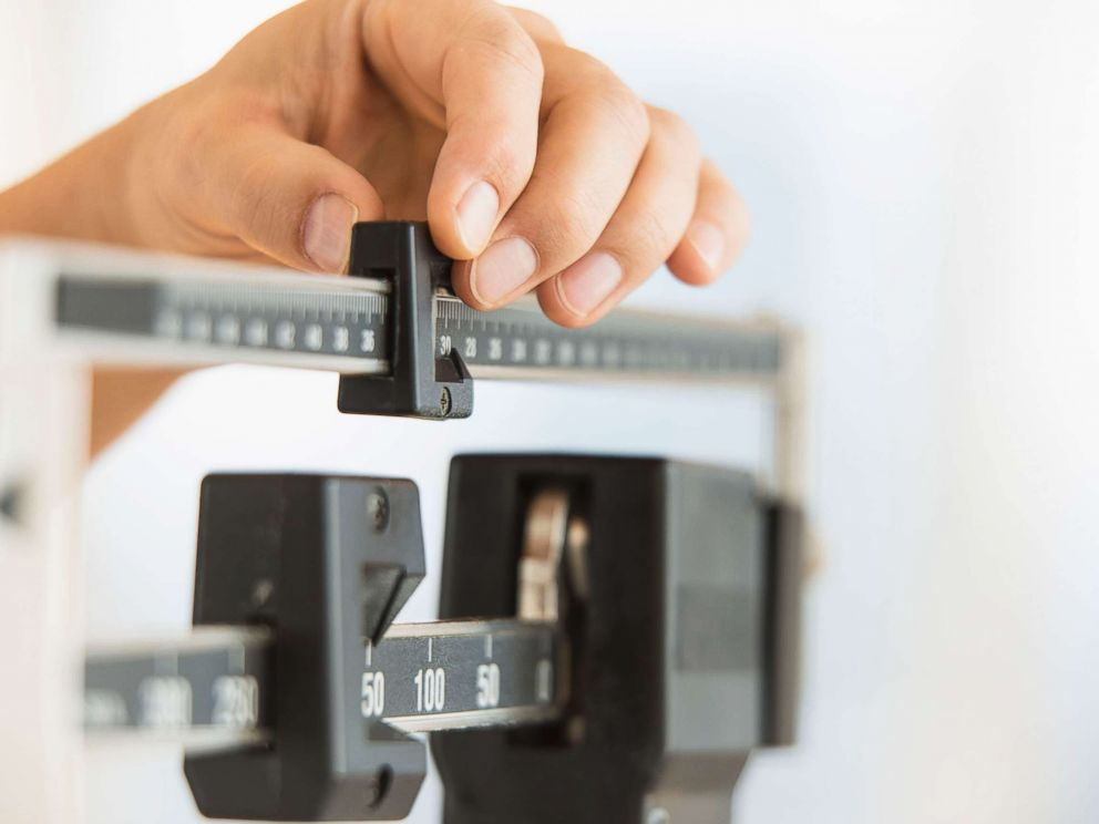 PHOTO: Stock photo of a person using a scale to weigh themselves.