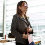 A woman stands in her office holding papers in this stock photo.