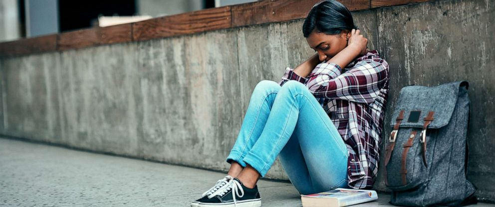 PHOTO: An undated stock photo depicts a young female college student sitting alone on campus.