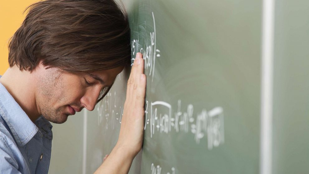 A college student is pictured leaning his head against a blackboard in this undated stock photo