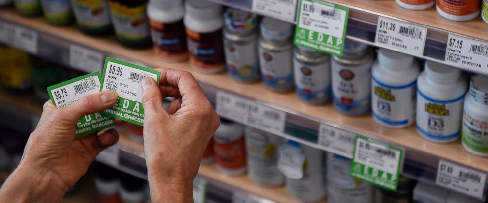 PHOTO: A store worker affixes price tags to vitamins at a grocery storey on July 26, 2017, in Denver.