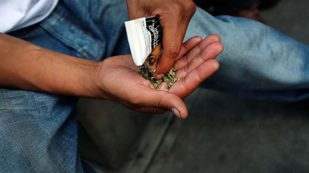 """A man prepares to smoke K2 or """"Spice"""", a synthetic marijuana drug, in East Harlem, Aug. 5, 2015 in New York City."""