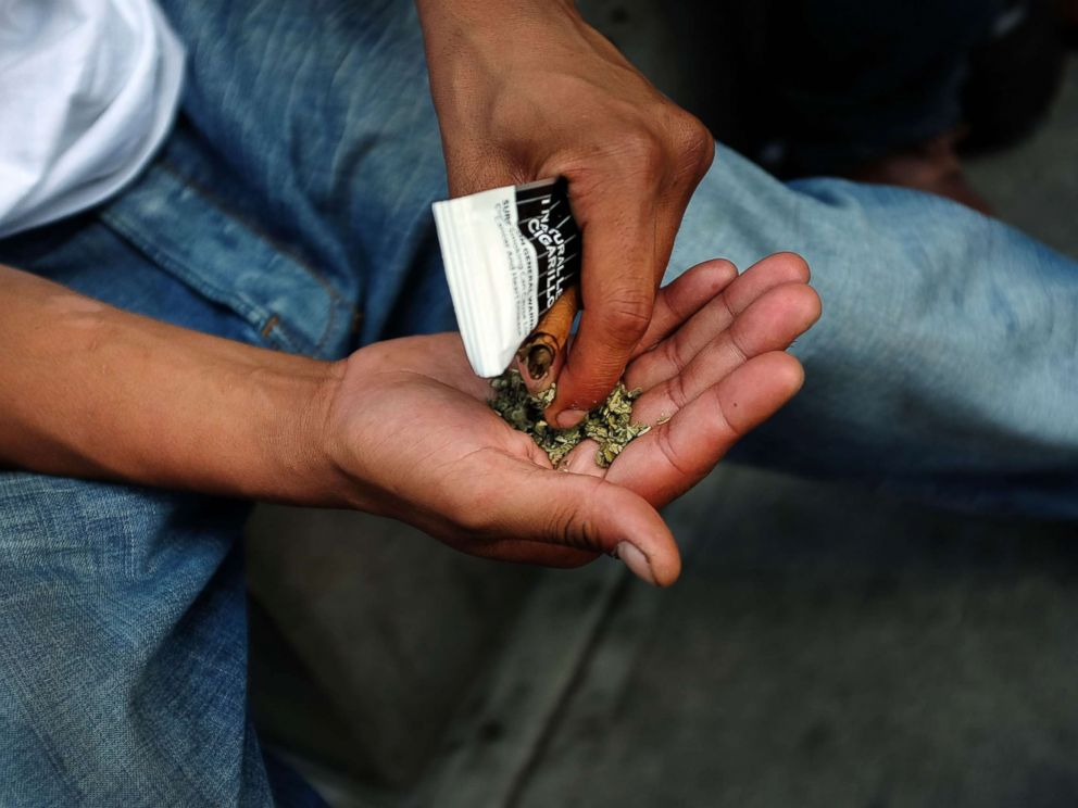 A man prepares to smoke K2 or Spice, a synthetic marijuana drug, in East Harlem, Aug. 5, 2015 in New York City.