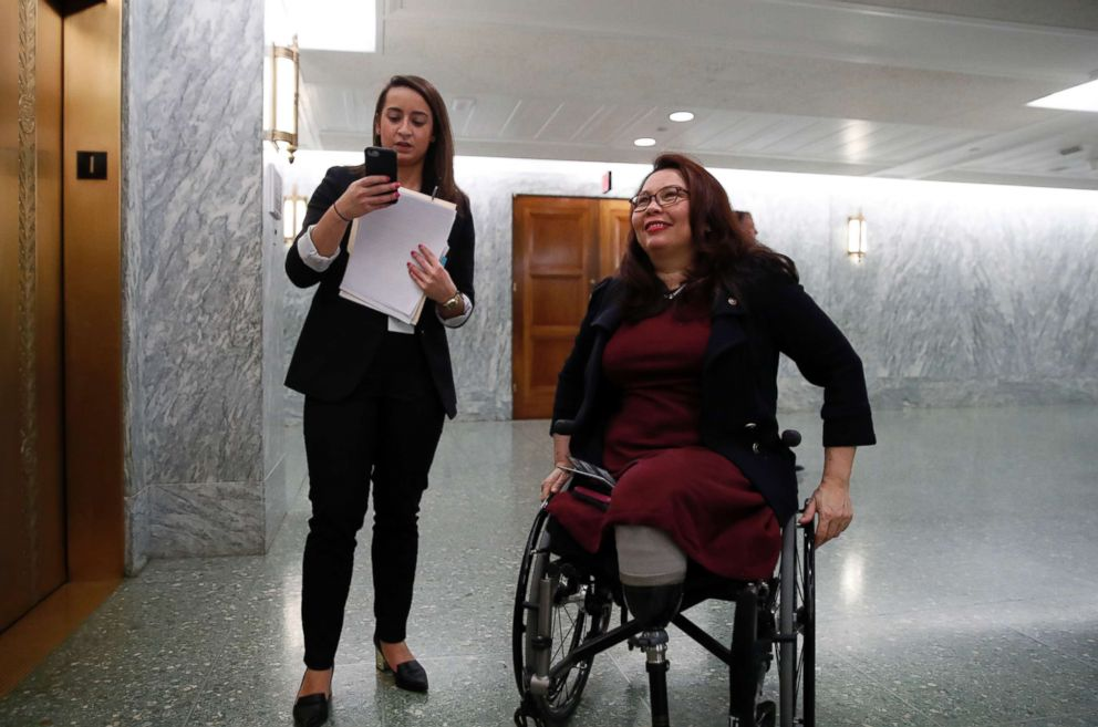PHOTO: Sen. Tammy Duckworth, D-Ill., right, waits with an aide for the elevator on Capitol Hill, Feb. 14, 2018 in Washington.