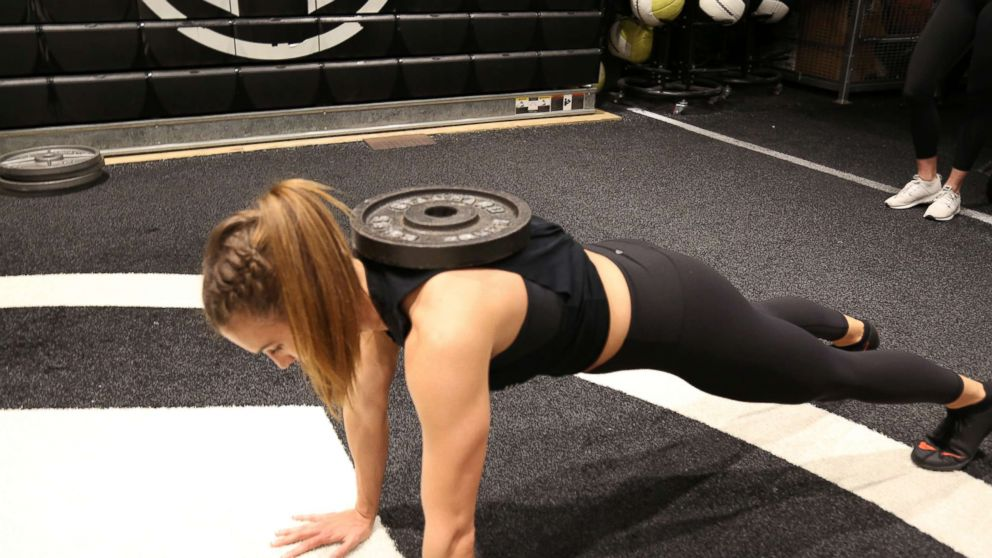 A Tone House trainer demonstrates a weighted push up.